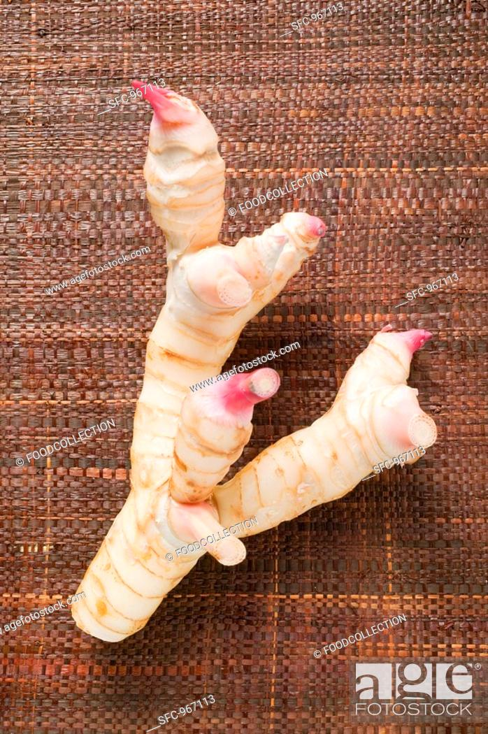 Stock Photo: Fresh galangal on brown fabric background.