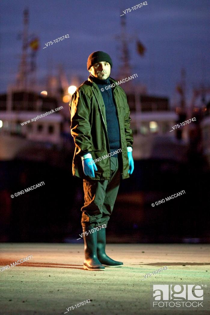 Stock Photo: Fisherman posing on harbour at dawn.