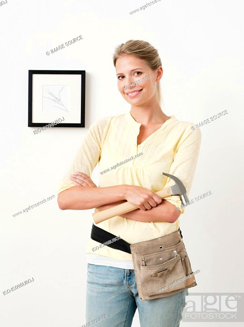 Stock Photo: Young woman with hammer and picture on wall.
