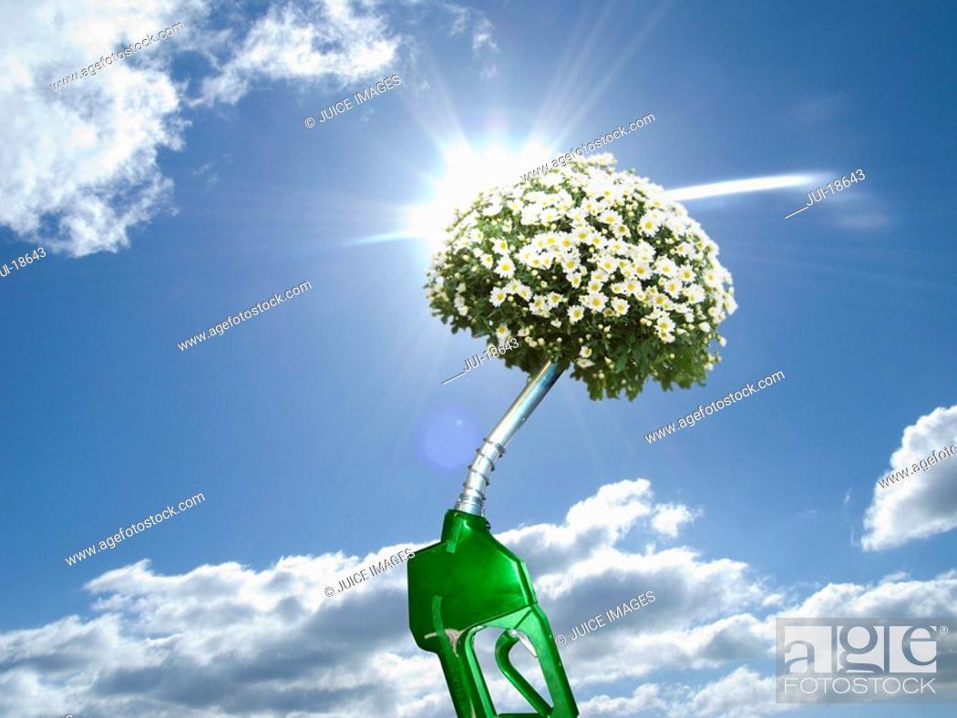 Stock Photo: Green gas pump with blooming plant at end of nozzle.