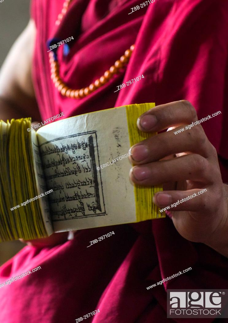 Stock Photo: Monk showing some tibetan scriptures printed from wooden blocks in the monastery traditional printing temple, Gansu province, Labrang, China.