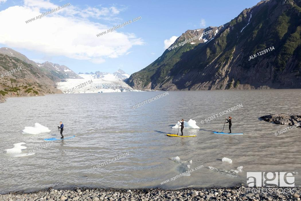 Imagen: Standup paddleboarders paddling on flatwater with the Grewingk glacier in the background, Kachemak Bay State Park, Southcentral Alaska.