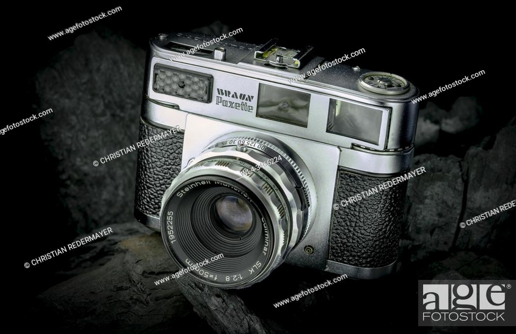 Stock Photo: A vintage camera painted with lights on black coals as background.