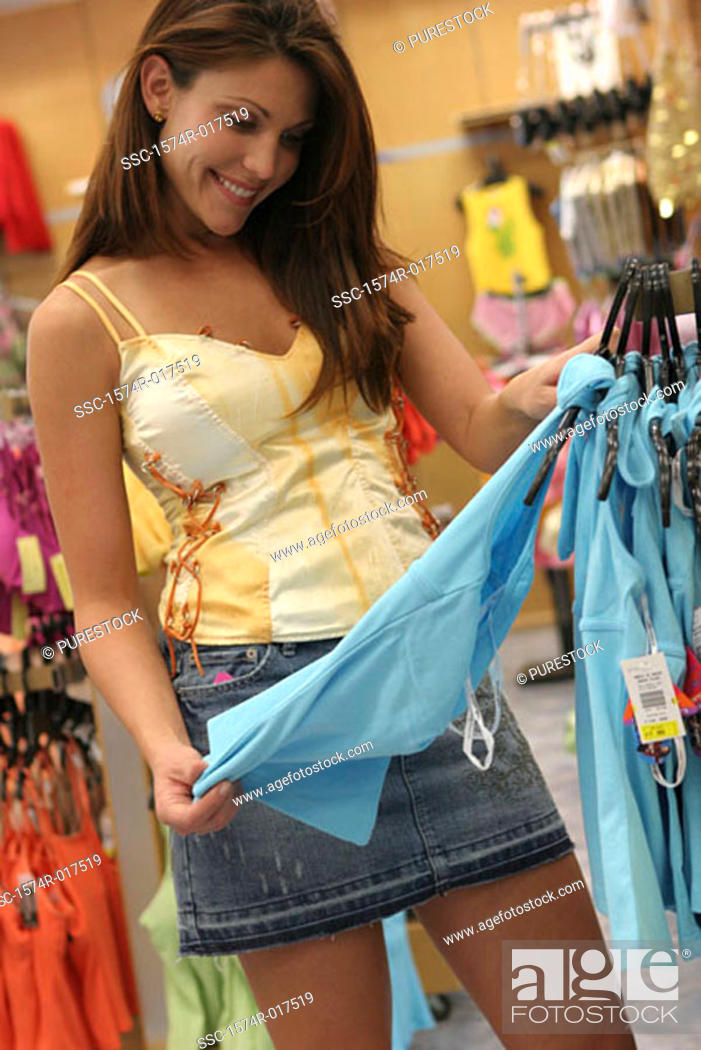 Stock Photo: Young woman selecting clothes in a clothing store.