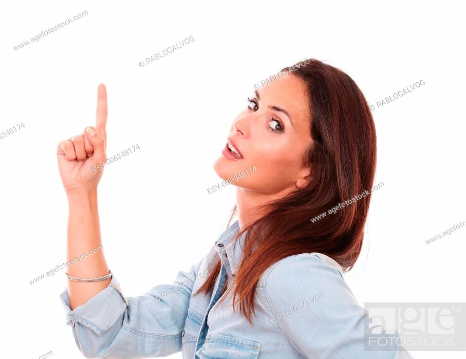 Stock Photo: Portrait of attractive female on blue shirt pointing up and looking at you on isolated white background - copyspace.