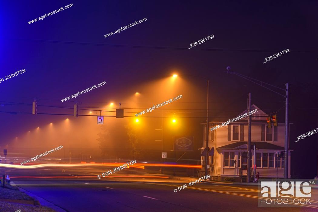 Stock Photo: Light traffic on main street (US 2) in the fog, before dawn, Ironwood, Michigan, USA.