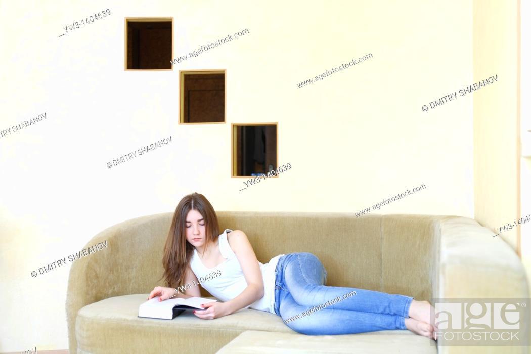 Stock Photo: Teen girl reading a book.