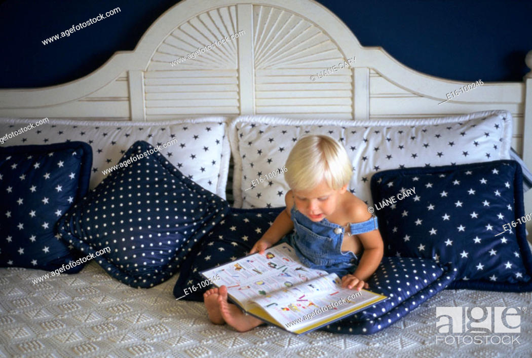 Stock Photo: Young boy reading on bed.