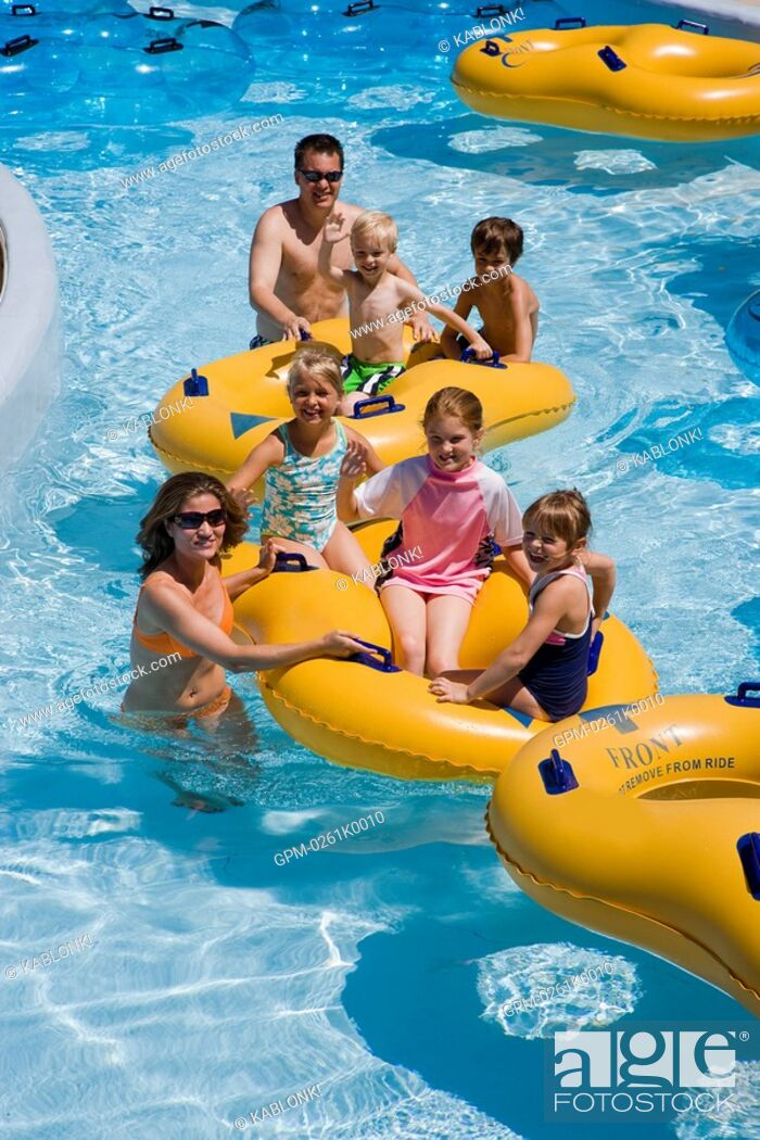 Imagen: Family and friends floating on innertubes at a water park.
