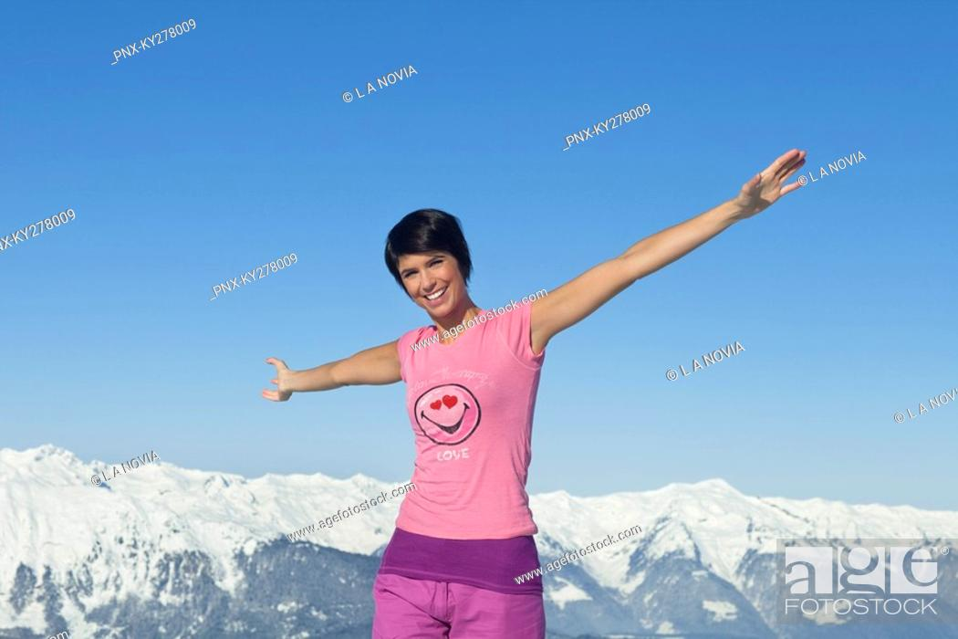 Stock Photo: Young woman with arms raised, smiling at camera, mountains in background.