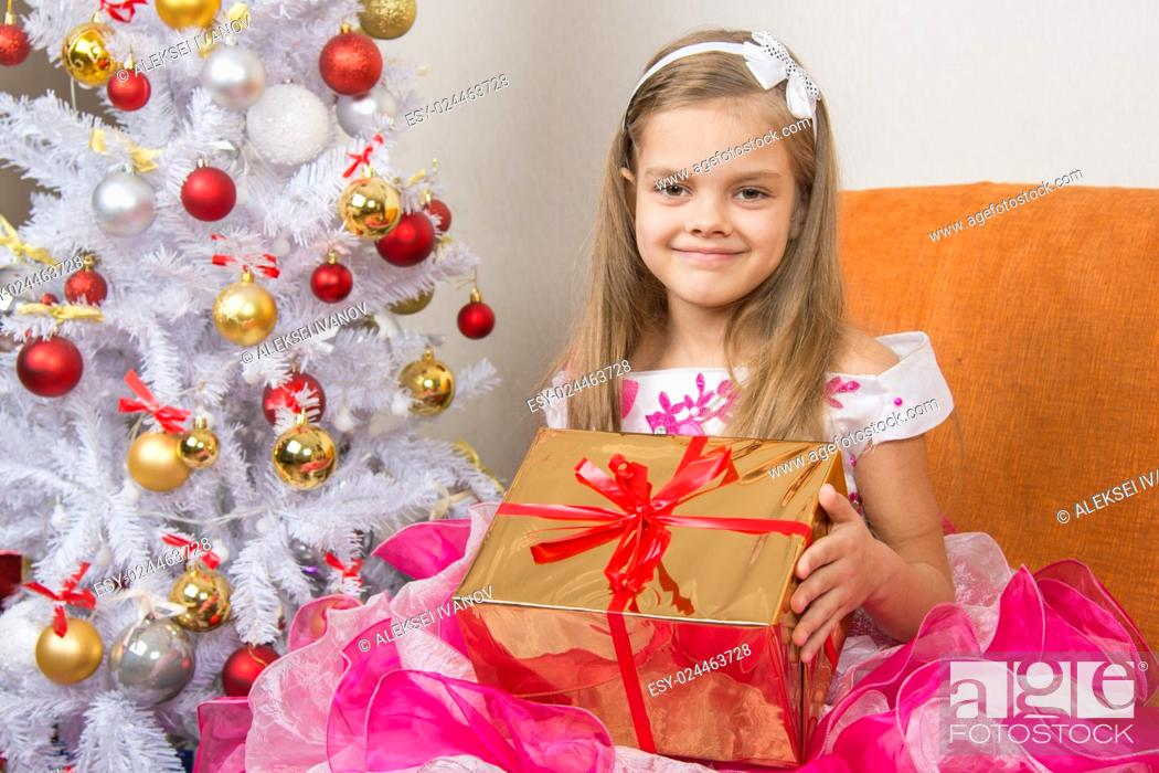 Stock Photo: girl in a beautiful dress gave New Year gift.