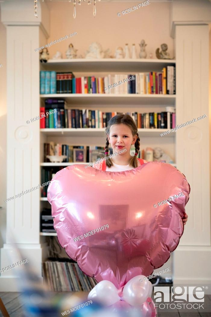 Stock Photo: Portrait of girl with braids holding big heart-shaped balloon.