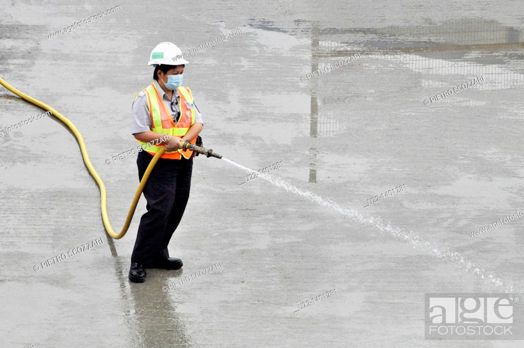 Stock Photo: Hong Kong: a man at work watering the pavement by the construction of the new pier on Victoria Harbour, in Central.