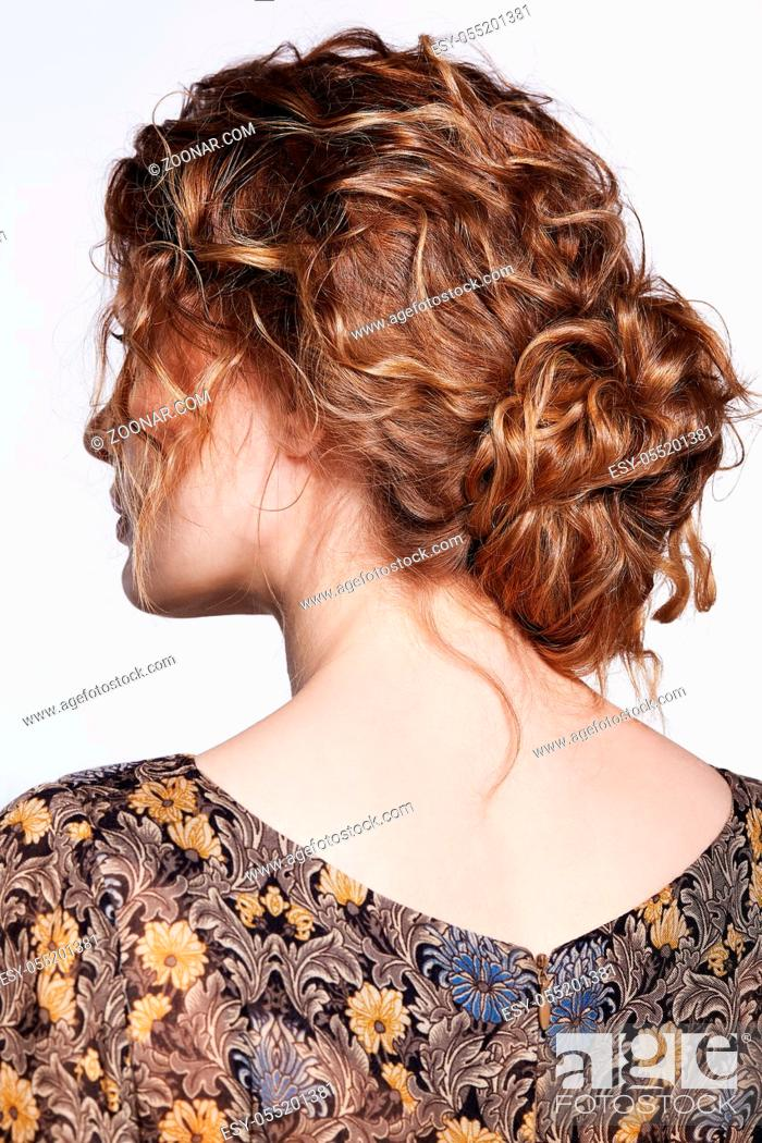 Stock Photo: Portrait of a young caucasian woman in vintage retro dress from back side. Female with wavy hair on a gray background. Girl long golden curly hair.