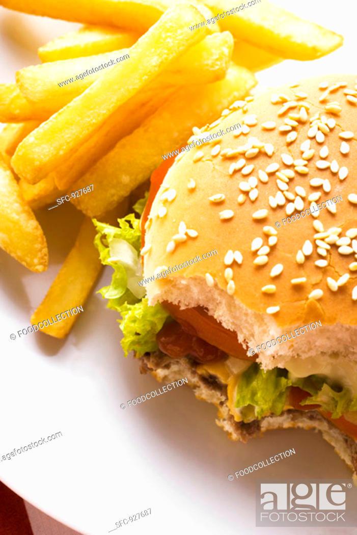 Stock Photo: Cheeseburger, bites taken, with chips.