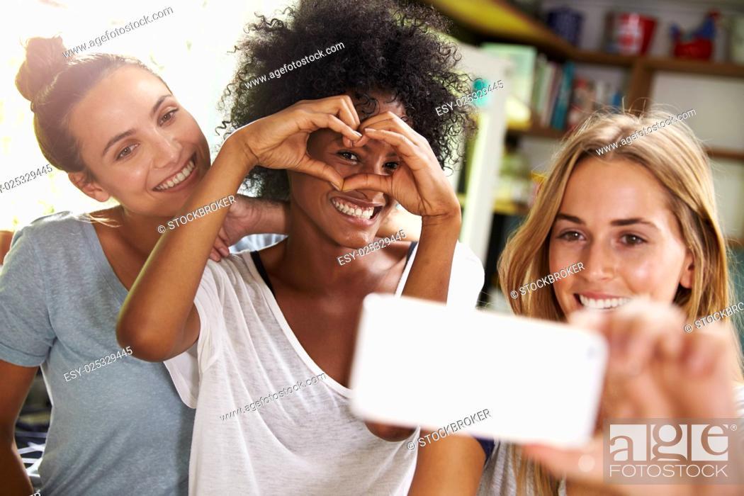 Stock Photo: Three Female Friends Taking Selfie Whilst Making Breakfast.