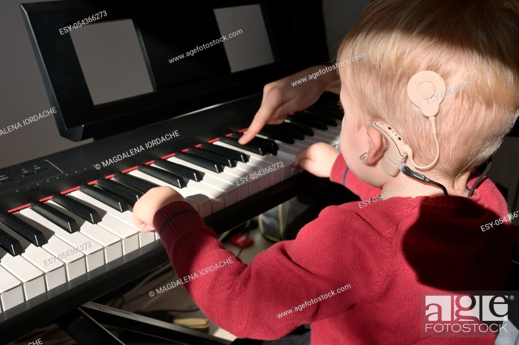 Stock Photo: A Boy With A Hearing Aids And Cochlear Implants Playing Piano.