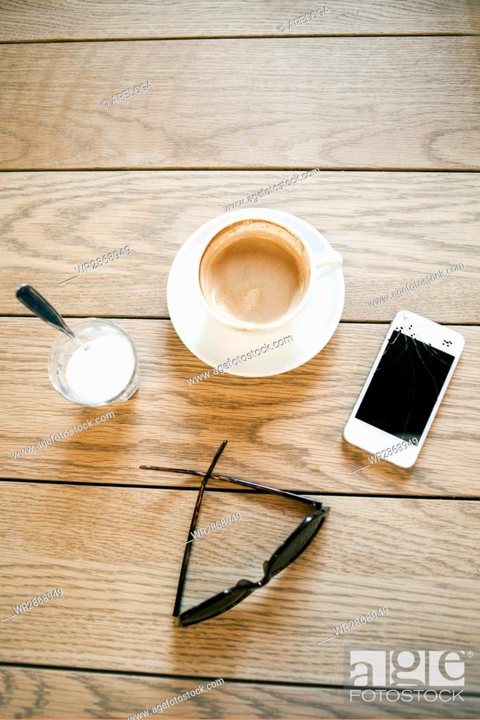 Stock Photo: Directly above shot of coffee cup with broken smart phone and eyeglasses on table.