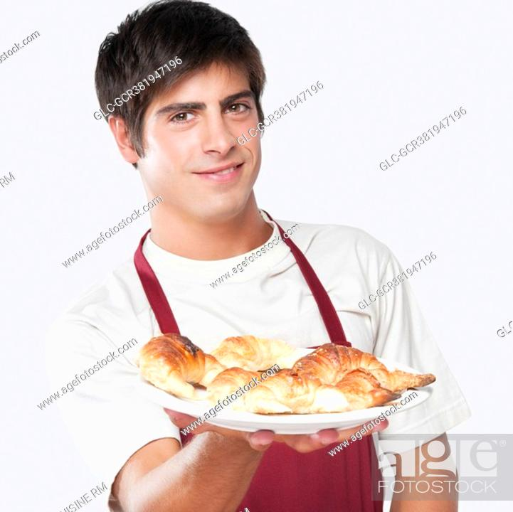 Imagen: Portrait of a man holding croissants on a plate.
