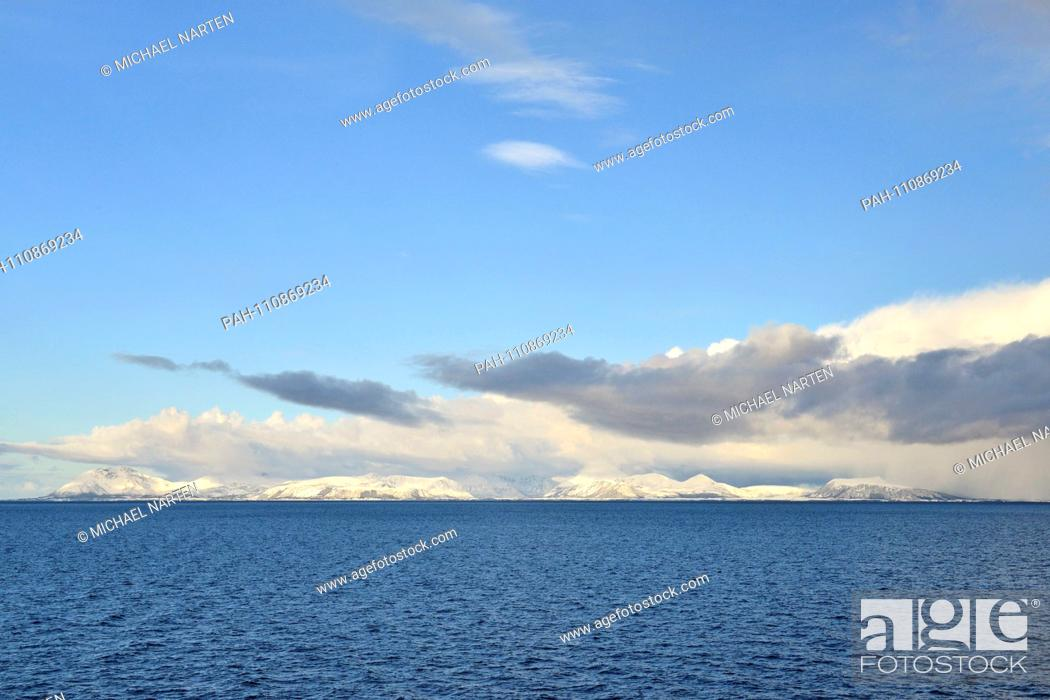 Stock Photo: The wide blue water area of Andfjorden with the snow-covered coast from the island Andøya on the horizon far away in the distance.