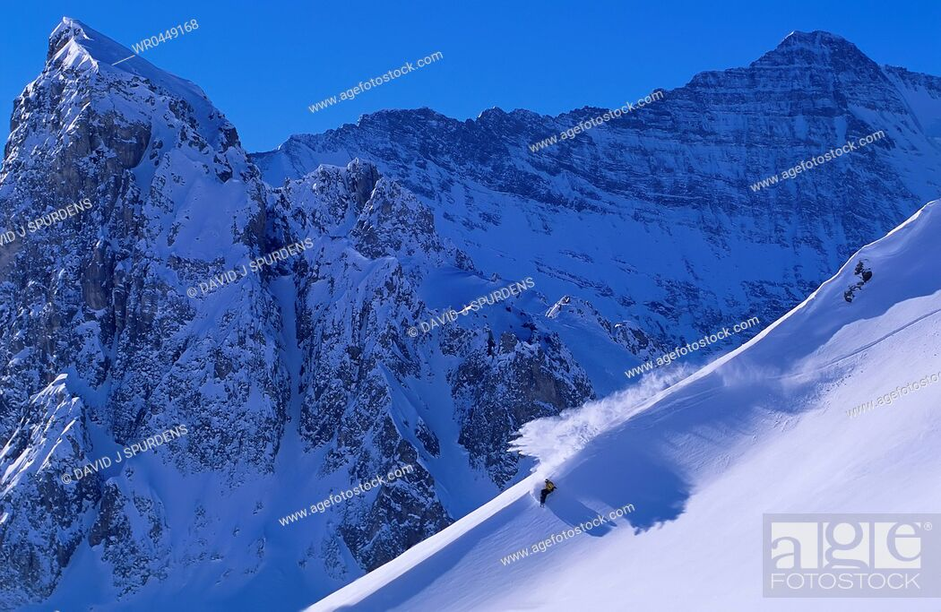 Stock Photo: A snowboarder riding fast down a spectacular snowy mountain.