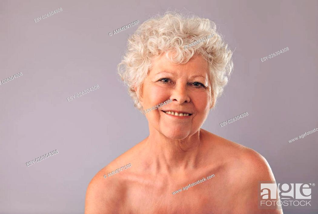 Stock Photo: Closeup of an attractive old lady with a sweet smile on her face. Senior woman smiling on grey background.