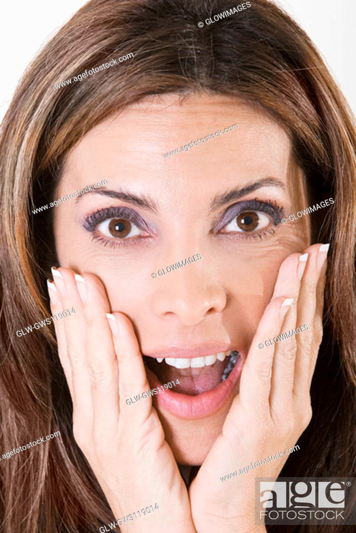 Stock Photo: Portrait of a young woman with her hands on her face.