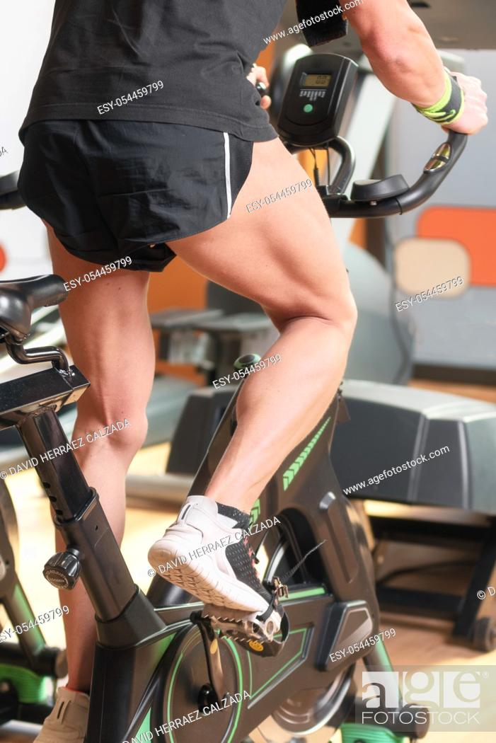 Stock Photo: Muscular man biking in the gym, exercising legs doing cardio workout cycling bikes, spinning class .