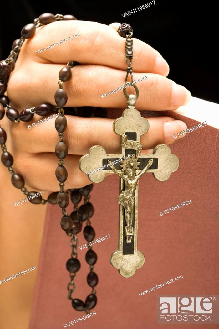Stock Photo: Woman holding Holy Bible open with rosary and crucifix in hand.