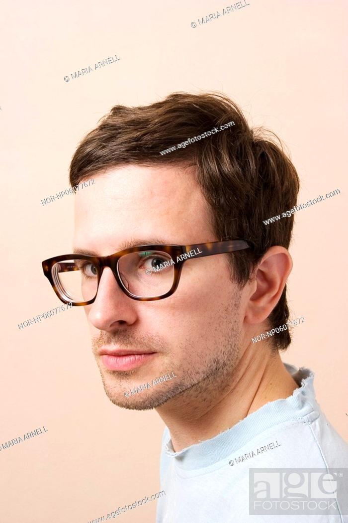 Stock Photo: Young man with retro glasses looking at the camera.
