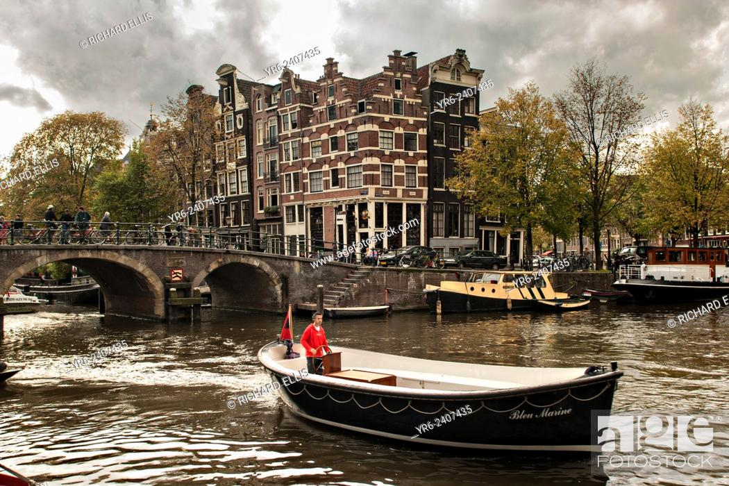 Stock Photo: A boat passes the Hemonybrug bridge at Keizersgracht and Leidsegracht in the Singel Canel in Amsterdam.