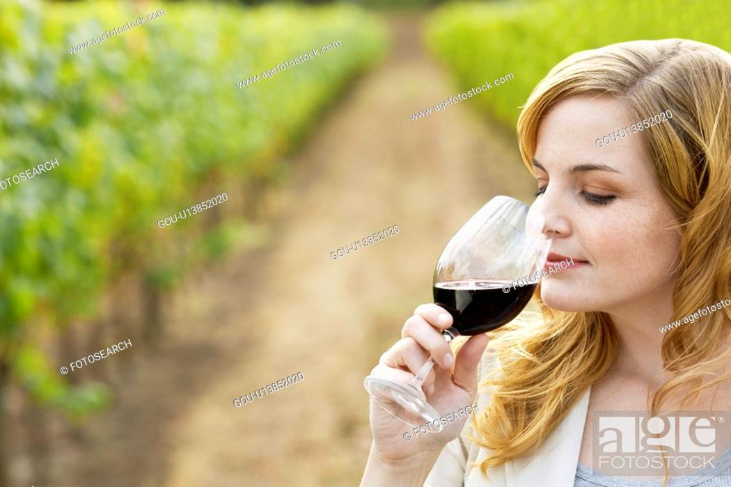 Stock Photo: Young woman smelling red wine in vineyard.