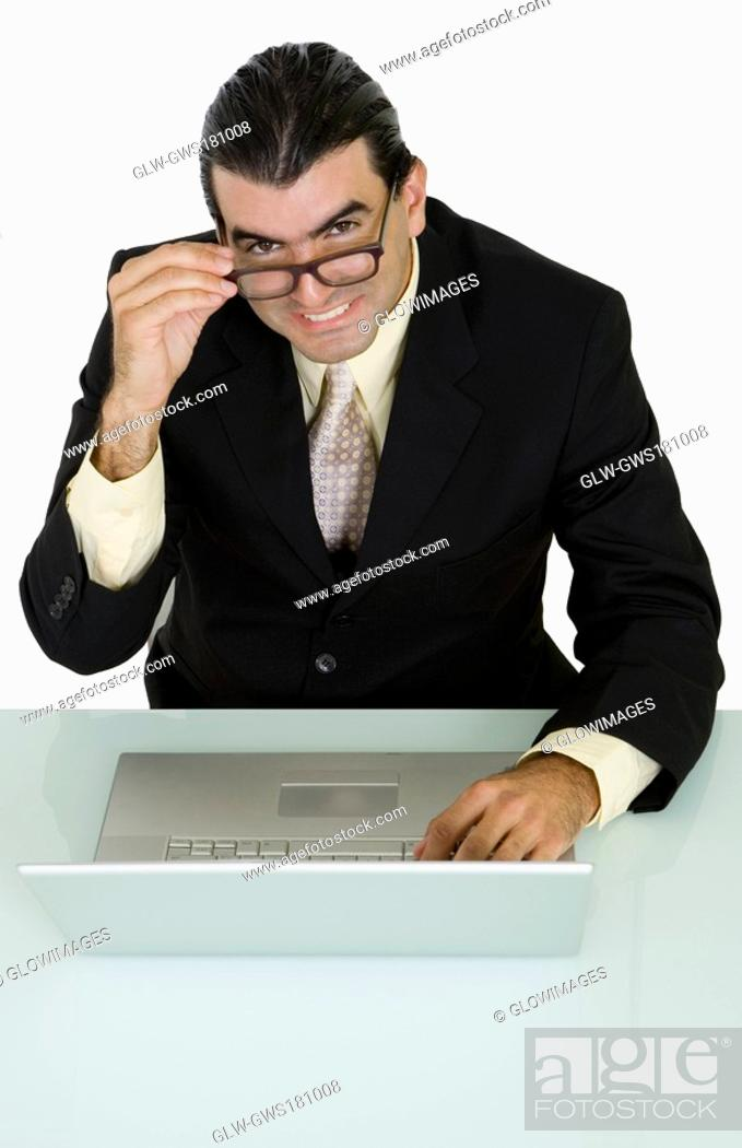 Stock Photo: Portrait of a businessman using a laptop and smiling.