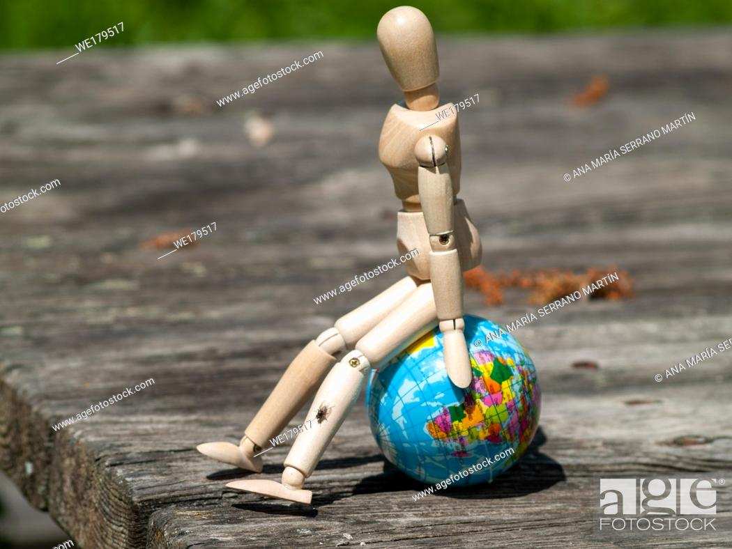 Stock Photo: A wooden mannequin sitting on a world ball. Concept of ecology, globalization.