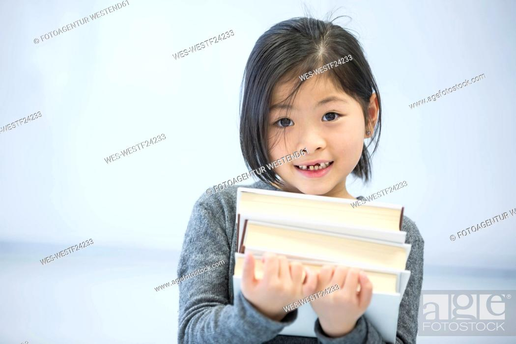 Stock Photo: Portrait of smiling schoolgirl carrying books in class.