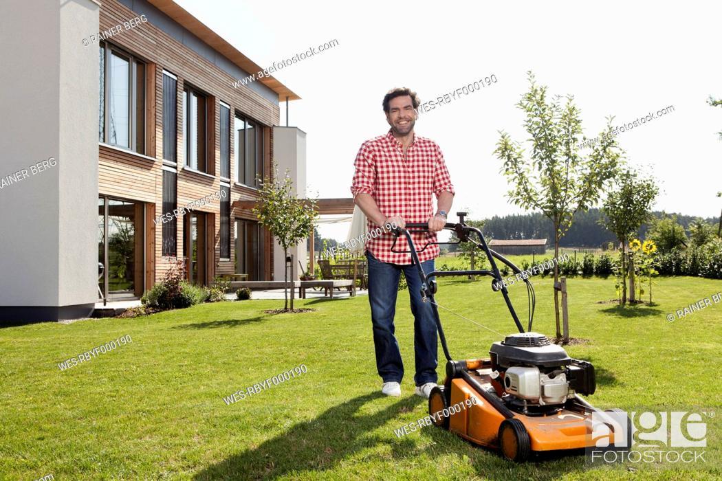 Stock Photo: Germany, Bavaria, Nuremberg, Mature man with lawn mower in garden.