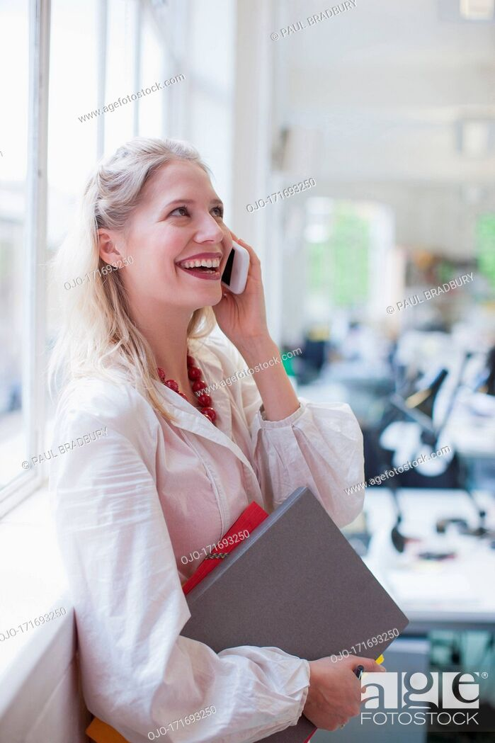 Stock Photo: Smiling businesswoman holding folders and talking on cell phone in office.