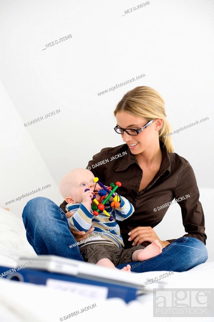 Stock Photo: Germany, Ammersee, Diessen, Young woman with baby boy 7 months sitting on bed, portrait.