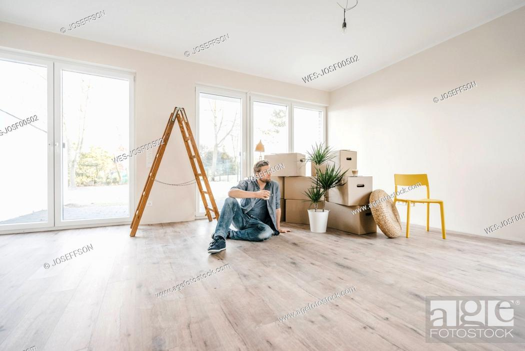 Stock Photo: Couple sitting on floor of their new home among moving boxes.