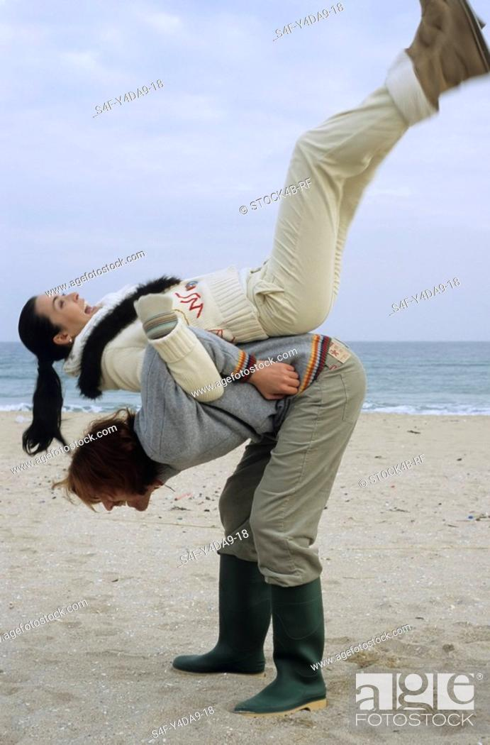 Stock Photo: Longhaired Man pulling his Girlfriend onto his Back - Fun - Physicalness - Relationship - Beach.