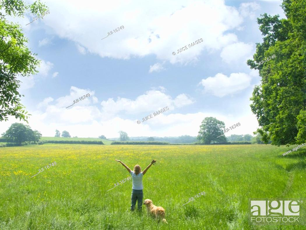 Stock Photo: Woman and dog standing in vast field.