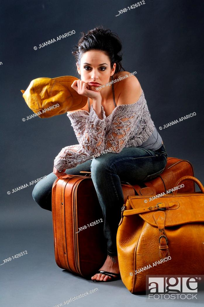 Stock Photo: Young woman posing, sitting in a studio with two suitcases of leather and leather yellow cap, looking straight at the camera with the face of boredom,.