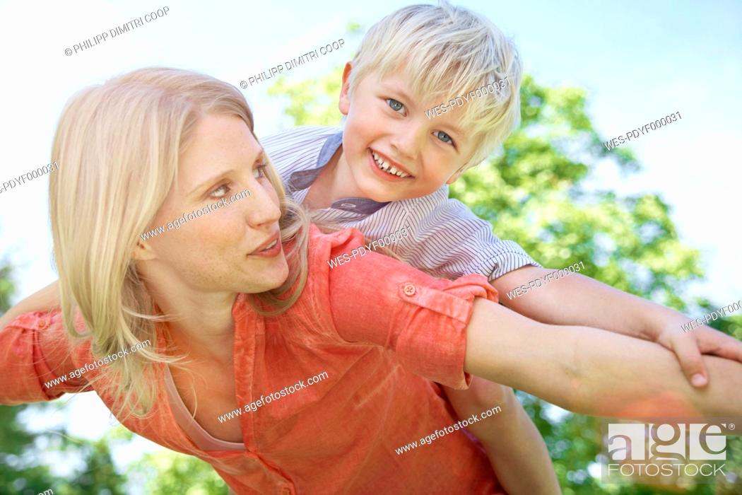 Stock Photo: Germany, Cologne, Mother and son flying, smiling.