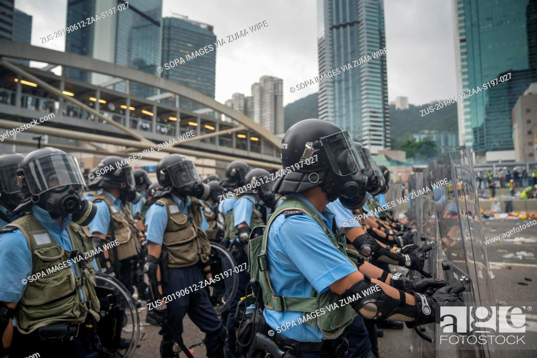 Stock Photo: June 12, 2019 - Hong Kong, China - A group of riot police seen with the riot gears and gas masks as they about to use tear gas to push the crowd back.