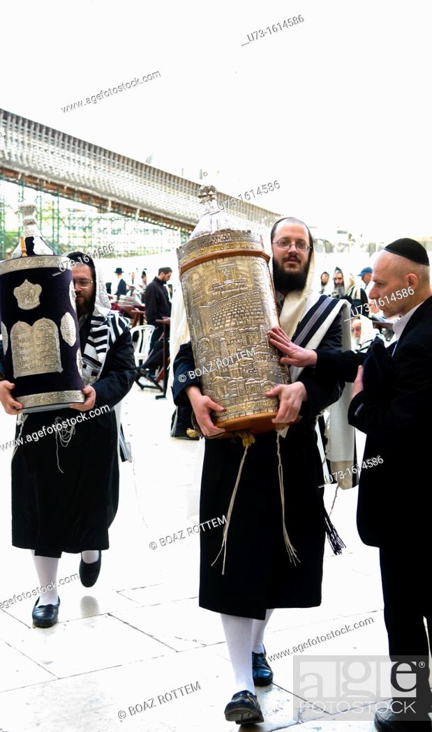 Stock Photo: Orthodox Jewish men holding Torah scroll books by the Wailing wall in the old city of Jerusalem.