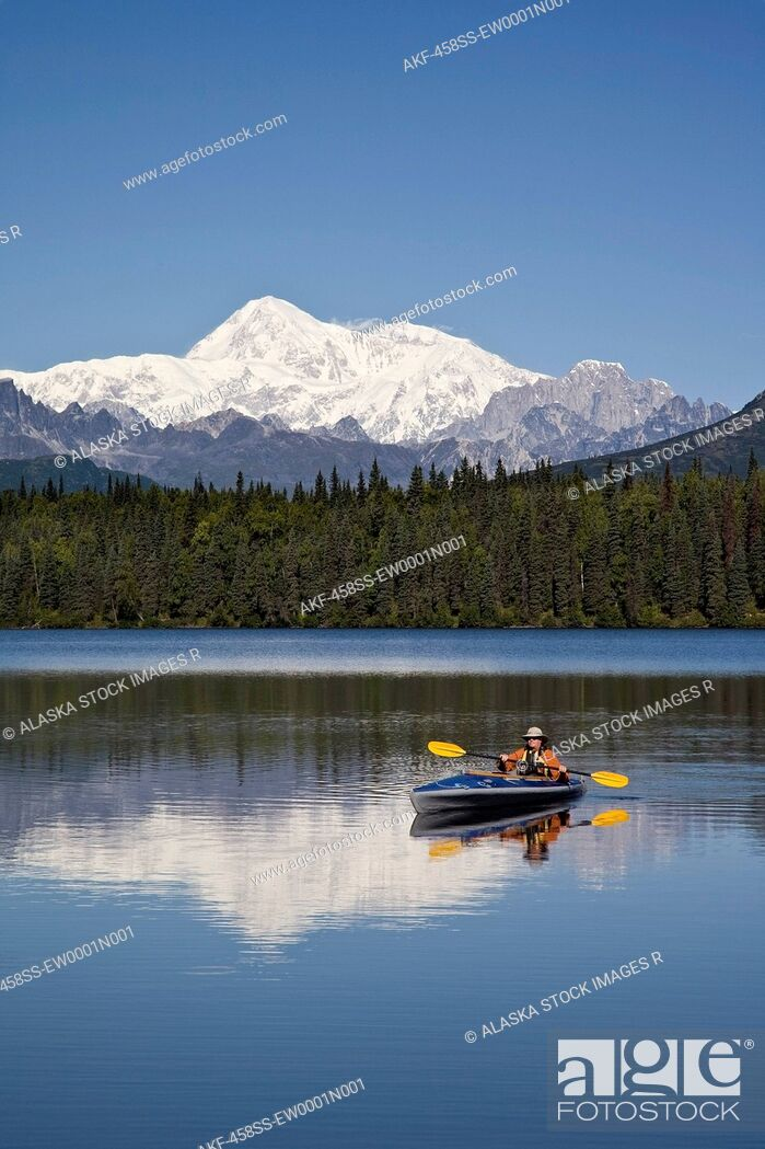 Stock Photo: Man paddling a Klepper kayak on Byers Lake at Denali State Park. Mt. McKinley is visible in the background. August. Summer in the interio of Alaska.