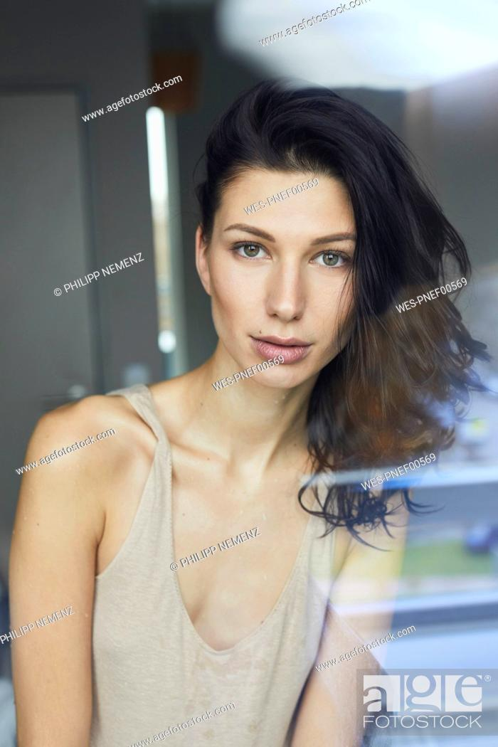 Stock Photo: Portrait of attractive dark-haired young woman behind windowpane.