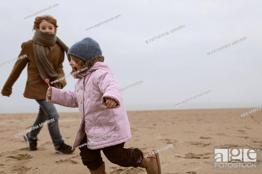 Stock Photo: Screaming little girl with lolly running on the beach in winter while her brother watching her.