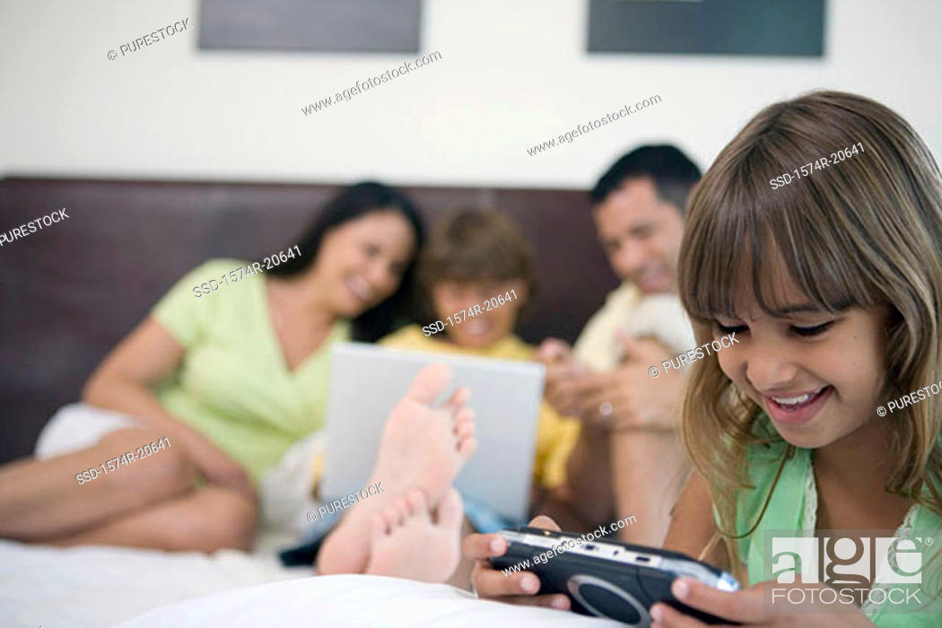 Stock Photo: Close-up of a girl playing a video game in the bed and her parents and brother behind him.