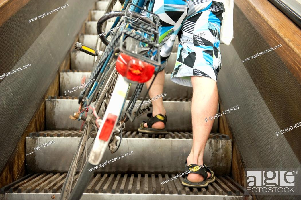 Stock Photo: Rotterdam, Netherlands. In the submerged Maastunnel there is a separate tube for pedestrians and bikers. They take a vintage.